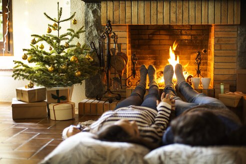 Couple holding hands resting by fireplace at home - CAVF47066