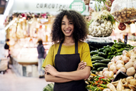 Portrait of confident owner with arms crossed standing at market stall - CAVF47117
