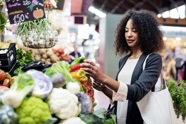 Woman buying vegetables in market - CAVF47132