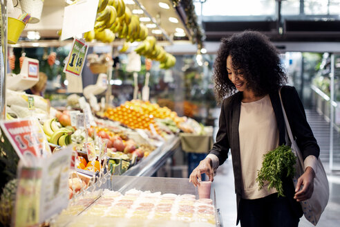 Woman buying juice while standing at store - CAVF47141