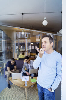 Businessman talking on mobile phone while colleagues discussing in background - CAVF47189