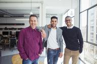 Portrait of happy businessmen standing by window in office - CAVF47231