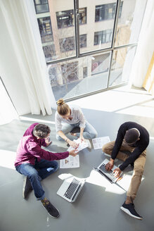 High angle view of business people working by window in office - CAVF47237