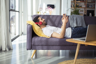 Happy businessman using tablet computer while lying on sofa in office - CAVF47246