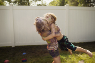 Siblings playing with colors on grassy field against wall - CAVF47294