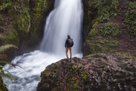 Rear view of man standing on rock against waterfall at Columbia River Gorge - CAVF47327