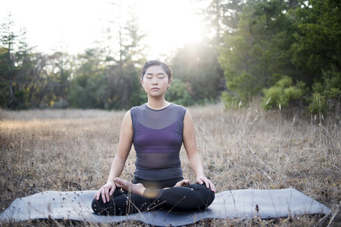 Woman meditating while sitting on exercise mat at field - CAVF47375