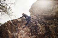 Low angle view of man jumping from rock on sunny day - CAVF47393