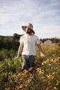 Thoughtful farmer walking in flowering field against sky - CAVF47402