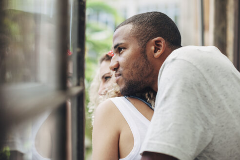 Close-up of thoughtful couple looking through window while standing at home - CAVF47561