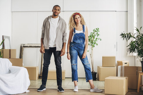 Portrait of smiling couple standing at new home - CAVF47564