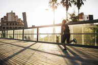 Rear view of woman jogging on bridge during sunset - CAVF47627