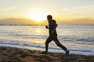 Teenage boy listening music while jogging at beach against sea during sunset - CAVF47747