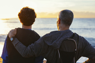 Father and son looking at view while standing at beach - CAVF47753