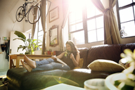 Woman reading book while having tea on sofa at home during sunny day - CAVF47762