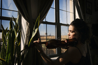 Thoughtful woman playing violin at home by window - CAVF47774
