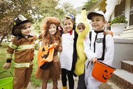 Happy children in Halloween costumes standing in yard during trick or treating - CAVF47786