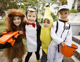 Cheerful children in Halloween costumes standing by house during trick or treating - CAVF47789