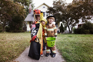 Portrait of smiling friends in Halloween costume standing against house during trick or treating - CAVF47801