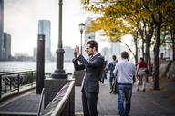 Businessman photographing through smart phone while standing on promenade in city - CAVF47828