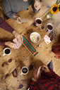 High angle view of friends playing cards while having coffee at home - CAVF47849