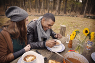 Happy couple having food while sitting at table in forest - CAVF47870