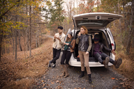 Friends relaxing by car on road amidst trees at forest during winter - CAVF47885