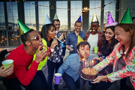 Man blowing candles on birthday cake held by woman while enjoying with friends at party - CAVF47891