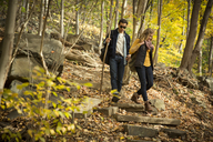Couple moving down steps in forest - CAVF47897