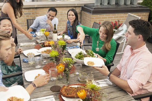 High angle view of friends having food at table on building terrace - CAVF47957