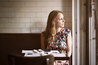 Thoughtful woman looking away while sitting in restaurant - CAVF47963