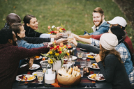 Happy friends toasting wine while sitting at table in backyard - CAVF47976