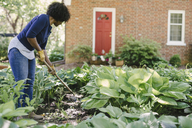 Woman using gardening fork while working in yard - CAVF48156
