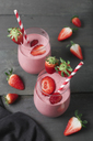 Glasses of strawberry smoothie and strawberries on dark wood - RTBF01199