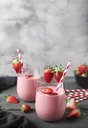 Glasses of strawberry smoothie and strawberries on dark wood - RTBF01202