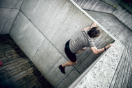Athlete climbing up concrete wall outdoors - DAWF00665
