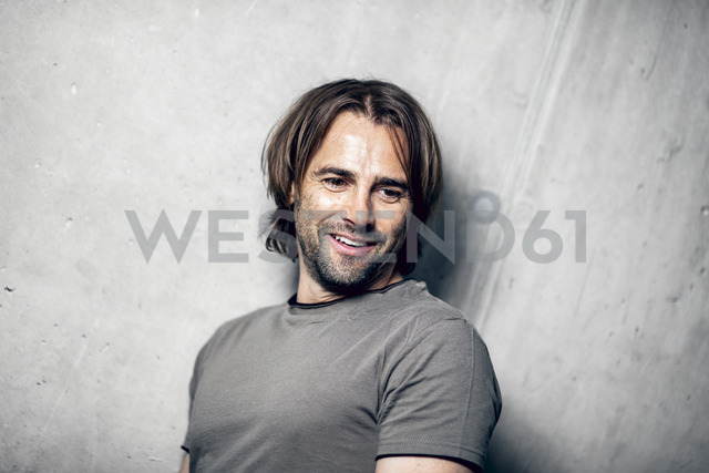 Portrait of smiling athlete at concrete wall - DAWF00668