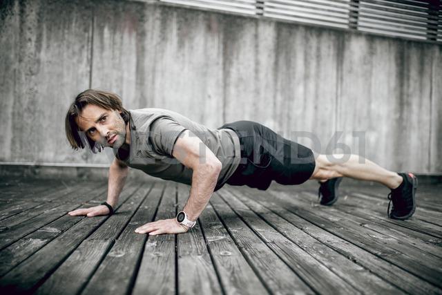 Athlete doing push ups outdoors - DAWF00671