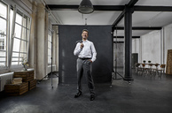 Portrait of mature businessman in front of black backdrop in loft - PDF01562