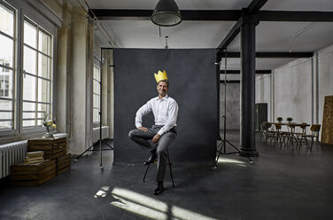 Portrait of mature businessman with crown in front of black backdrop in loft - PDF01565