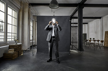 Mature businessman holding refecting mirror in front of black backdrop in loft - PDF01568