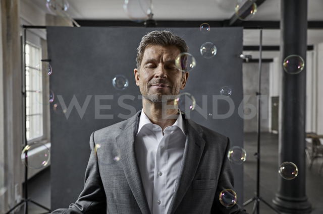Portrait of mature businessman with bubbles in front of black backdrop in loft - PDF01571