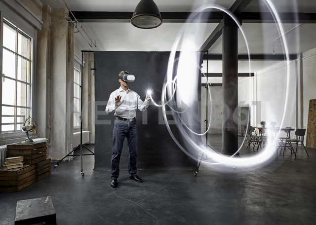 Mature man with vr glasses light painting in front of black backdrop in loft - PDF01574 - Philipp Dimitri/Westend61