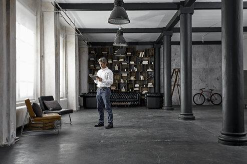 Mature man using digital tablet in loft flat - PDF01580
