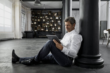 Mature man sitting on the floor using digital tablet in loft flat - PDF01583