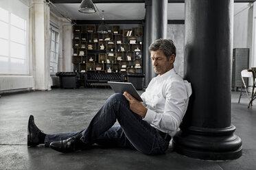 Mature man sitting on the floor using digital tablet in loft flat - PDF01583