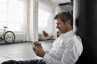 Mature man sitting on the floor using smartphone in loft flat - PDF01586