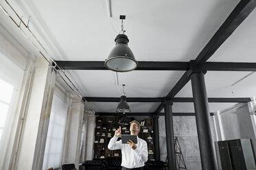 Mature man using digital tablet in loft flat - PDF01589