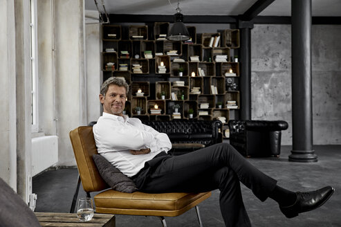 Portrait of mature man sitting on chair in loft - PDF01598