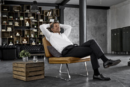 Mature man sitting on chair in loft relaxing - PDF01601